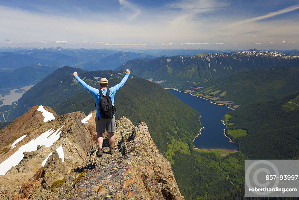 Hiker celebrating in victory pose after climbing Lady Peak in CheamMountain Range