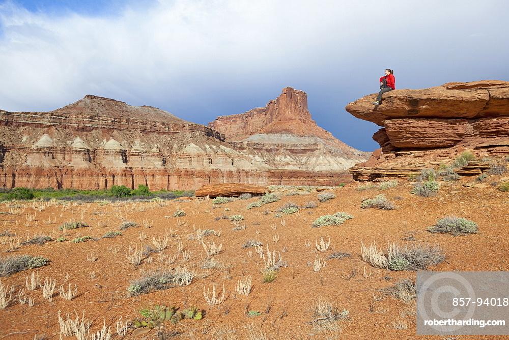 A woman sits on a bedrock terrace at Saddle Horse Bottom below tall canyon walls in Canyonlands National Park, Utah.
