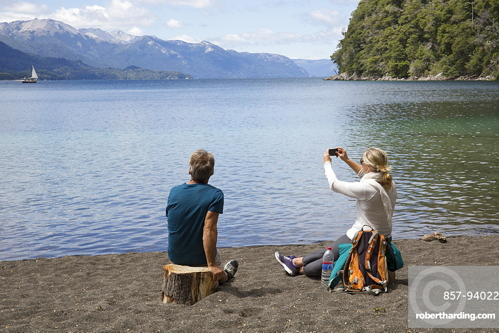 Mature couple take photo on beach by mountain lake