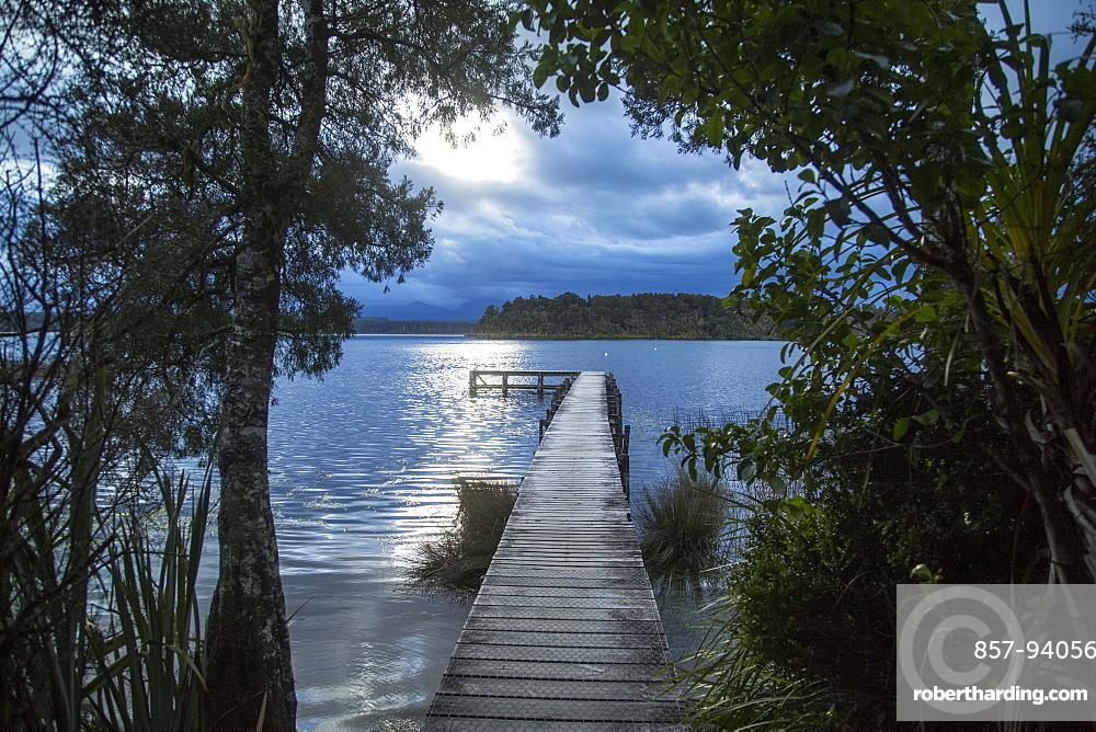Wooden Dock On Lake During Sunset