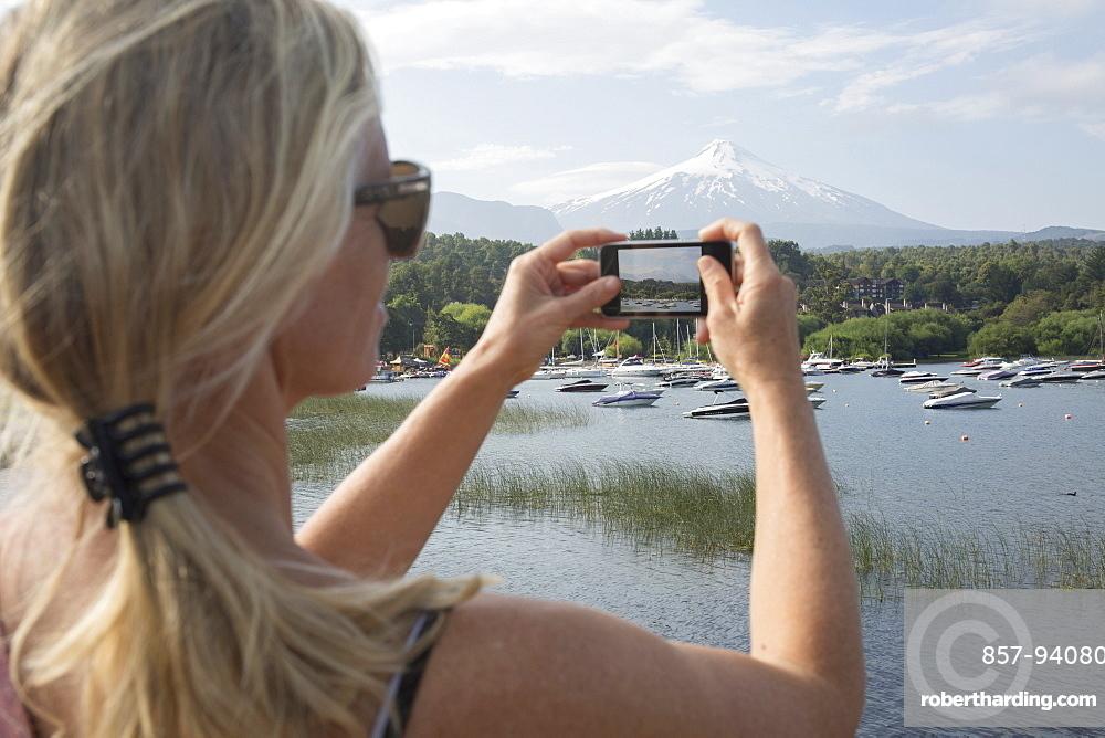 Woman takes smart phone pic over lake, Villarica volcano