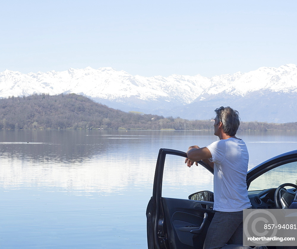 Mature man relaxes on door of car by lake