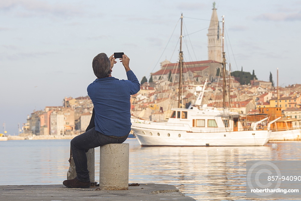 Man takes photo across harbour to old town of Rovinj at sunset