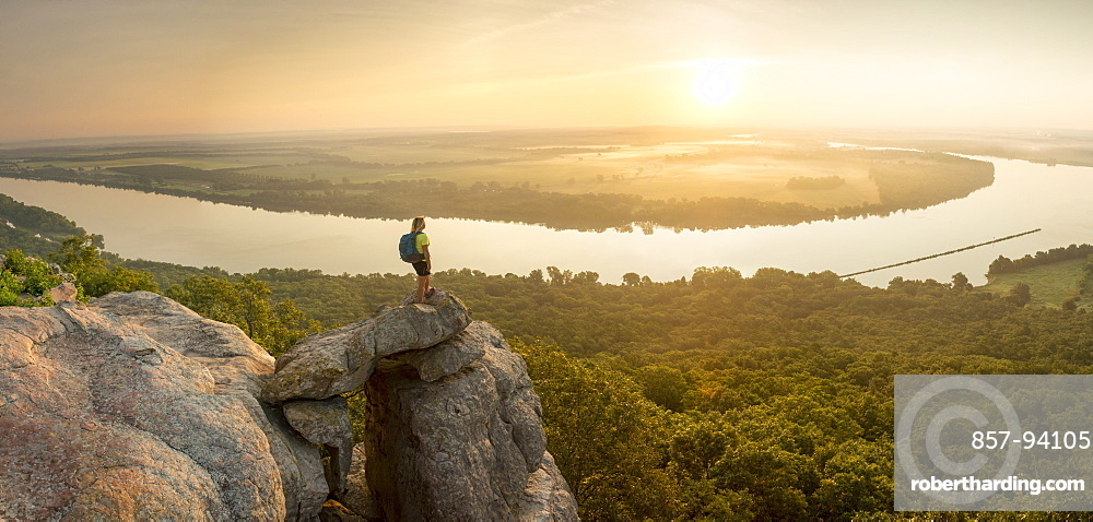 Woman standing on sandstone overhang watching sunrise from summitofPetitJean Mountainabove Arkansas River Valley
