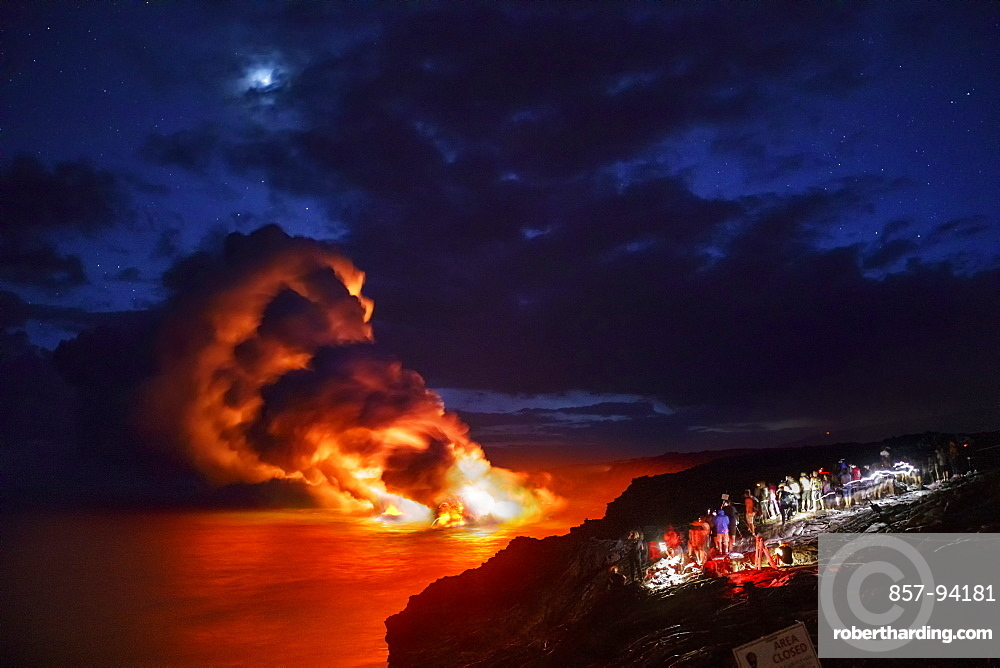 Tourists viewing lava from Kilauea Volcano pouring into ocean atKamokuna