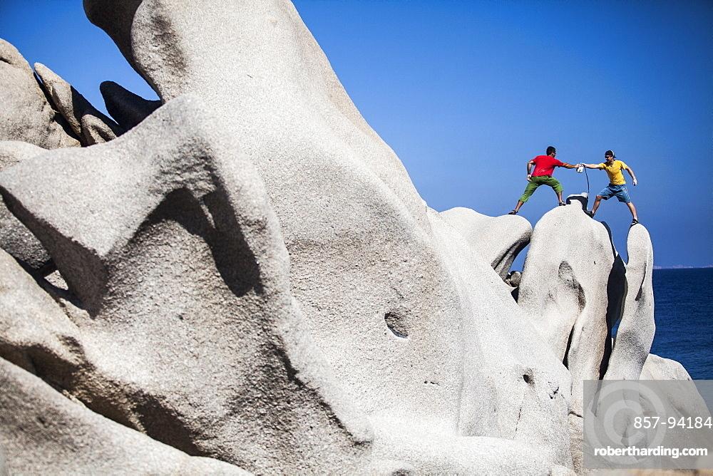 Men climbing on rock near sea, CapoTesta, Sardinia, Italy