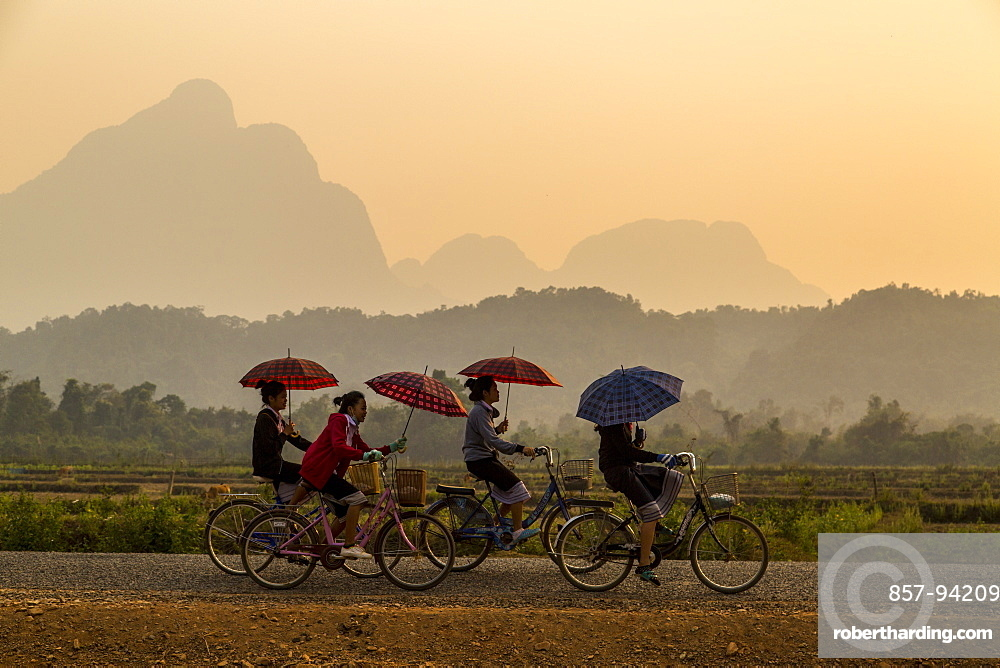 A Group Of Girls Riding By Bike From School Holding An Umbrella In Northern Laos
