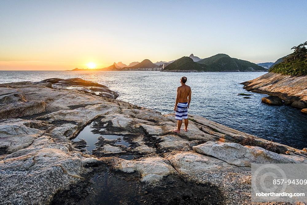 Man watching the sunset from Ilha de Cotunduba (Cotunduba Island) in Rio de Janeiro, Brazil