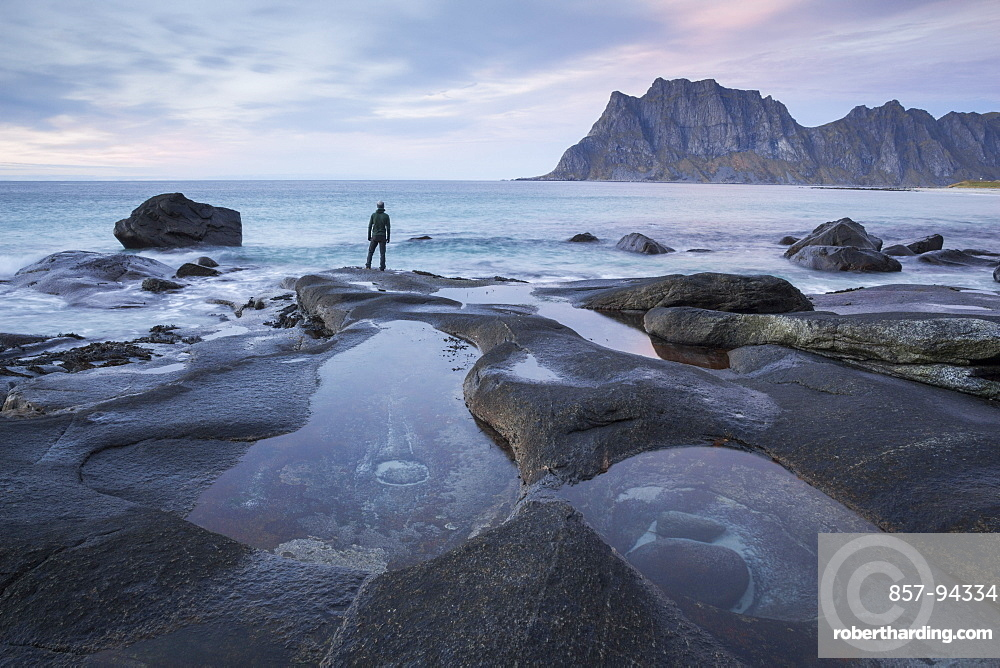Man with beanie standing at the edge of a rocky beach and looking contemplatively towards a mountain in the distance.