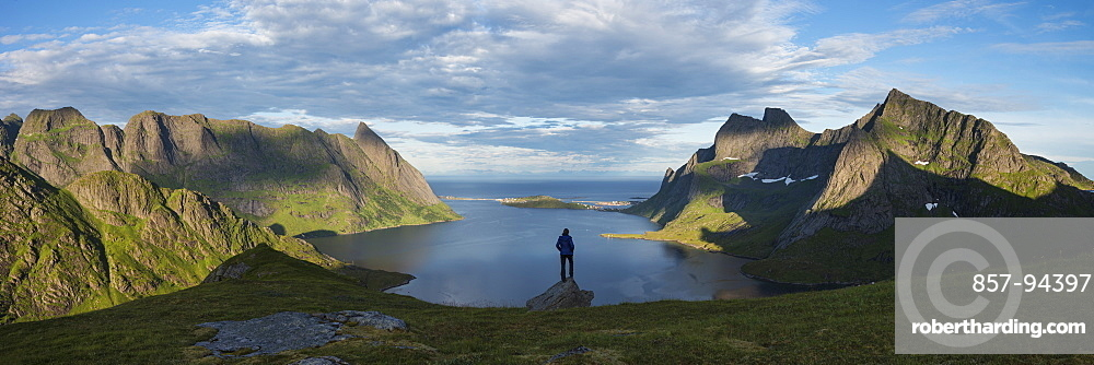 Female hiker takes in panoramic view over Reinefjord and surrounding mountains, near Vindstad, Moskenesøy, Lofoten Islands, Norway