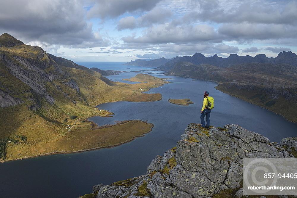Female hiker takes in view over Selfjord from summit of Tverrfjellet, Lofoten Islands, Norway
