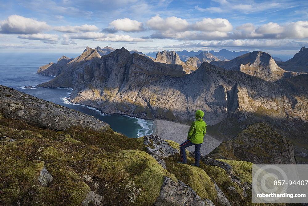 Female hiker takes in view over Bunes beach while hiking to Storskiva mountain peak, Moskenesøy, Lofoten Islands, Norway