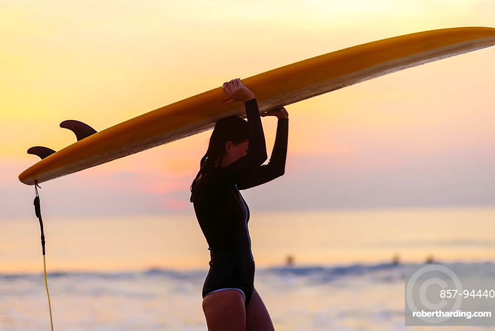 Female surfer carrying board above head at sunrise