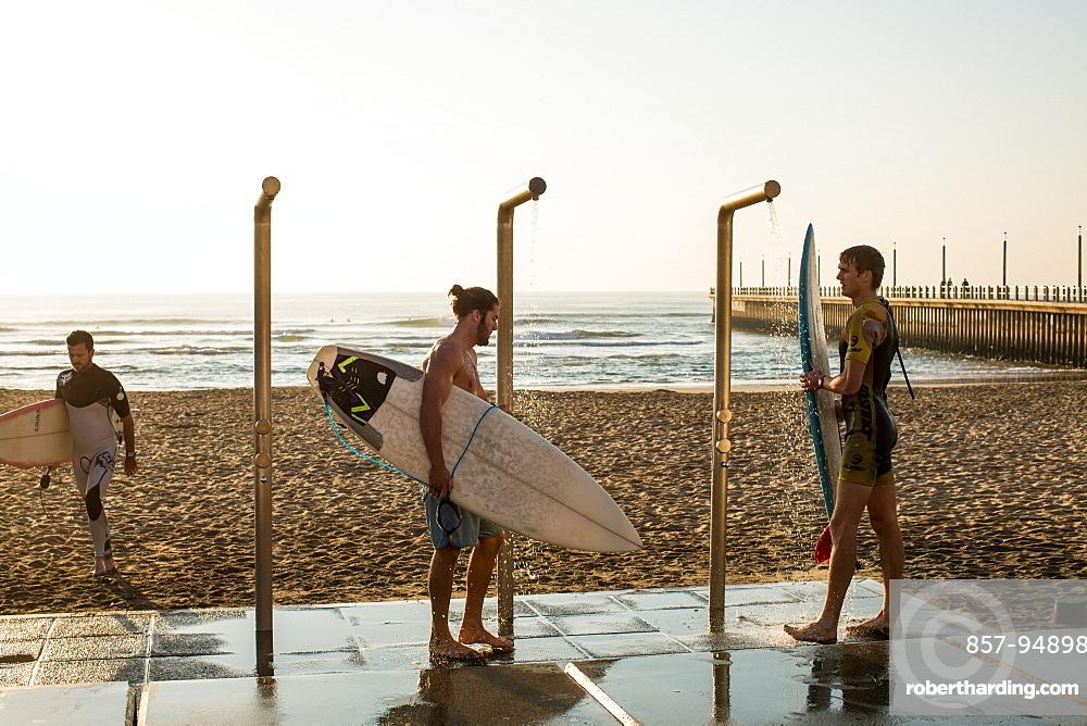 Men washing down surfboards near promenade on Golden Mile in Durban, South Africa