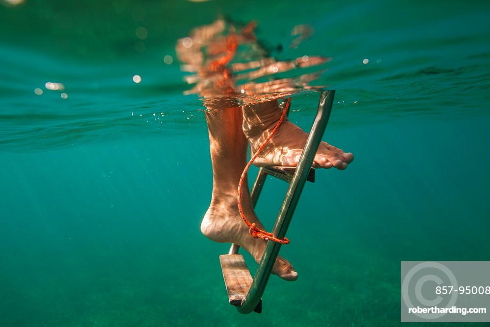 A man climbs down a ladder underwater off a boat near Utila Island, Honduras.