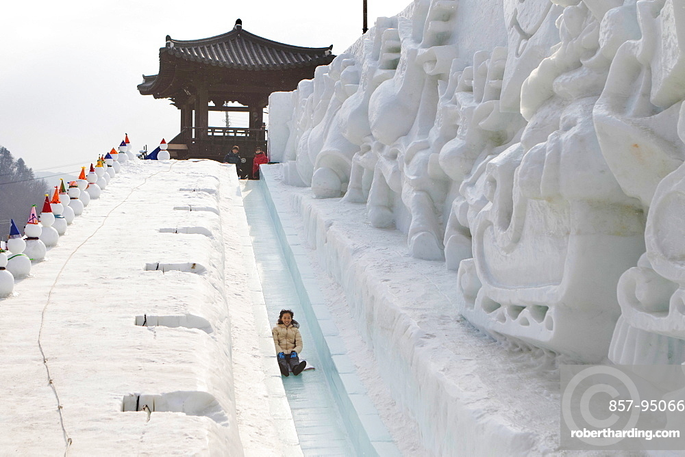 An Asian woman is having fun sledding down a steep ice slope. Hwacheon Sancheoneo Ice Festival. Gangwon-do, South Korea.  The Hwacheon Sancheoneo Ice Festival is a tradition for Korean people. Every year in January crowds gather at the frozen river to celebrate the cold and snow of winter. Main attraction is ice fishing. Young and old wait patiently over a small hole in the ice for a trout to bite. In tents they can let the fish grilled after which they are eaten. Among other activities are sledding and ice skating. The nearby Pyeongchang region will host the Winter Olympics in February 2018.
