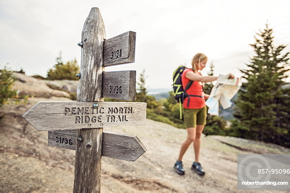 A woman consults her trail map next to a trail sign while hiking in Acadia National Park, Maine.