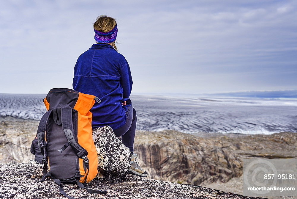 Rear view of woman sitting with backpack and looking at view of glacier, Narsaq, Greenland