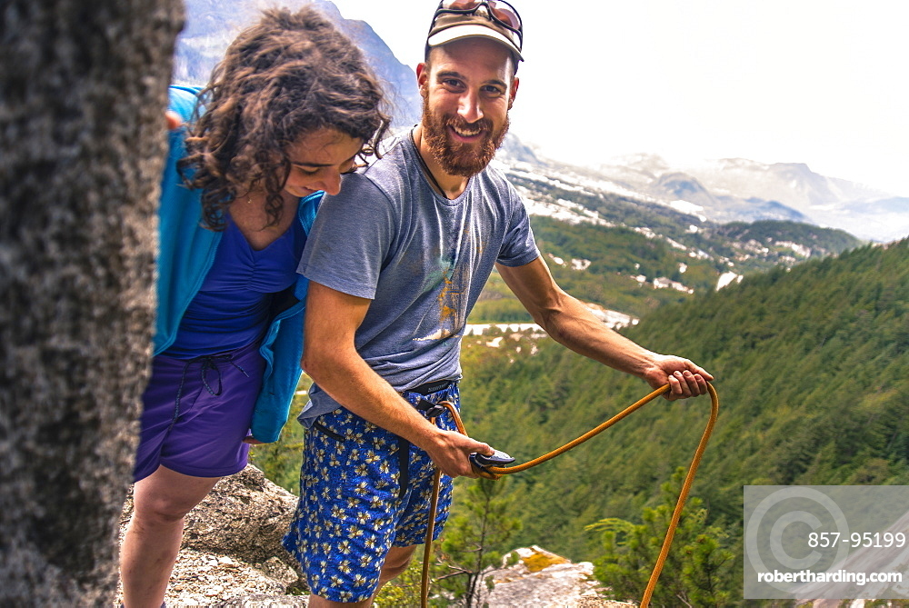 Two adventurous smiling female and male rock climbers in mountains, Squamish, British Columbia, Canada
