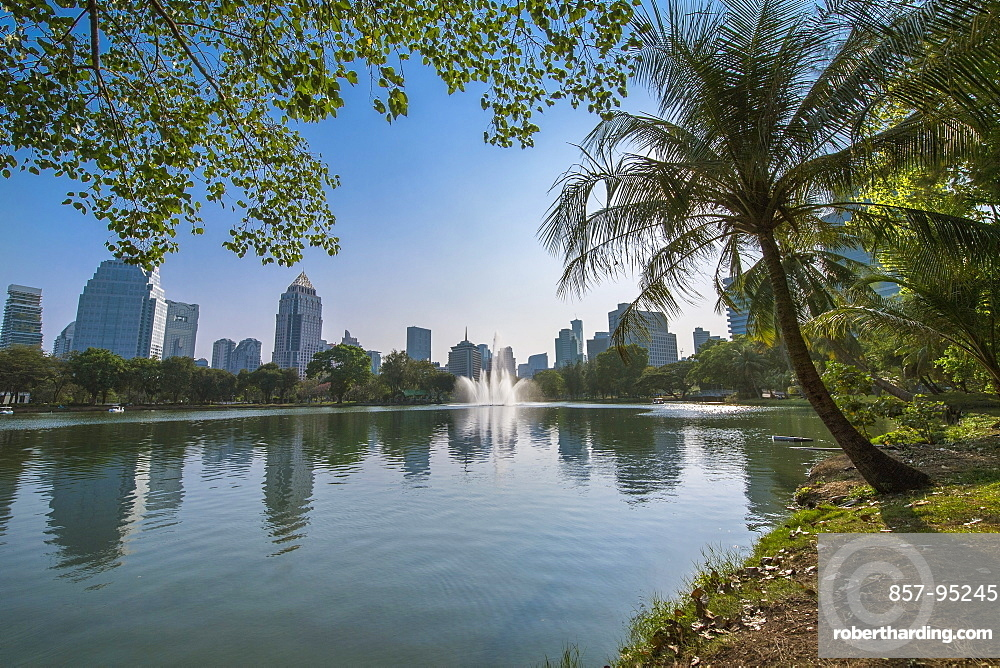 View of fountain in lake at Lumphini Park under clear sky and skyline of city of Bangkok, Thailand