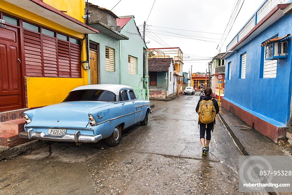 Rear view of female tourist walking on street by vintage car in Baracoa, Guantanamo Province, Cuba
