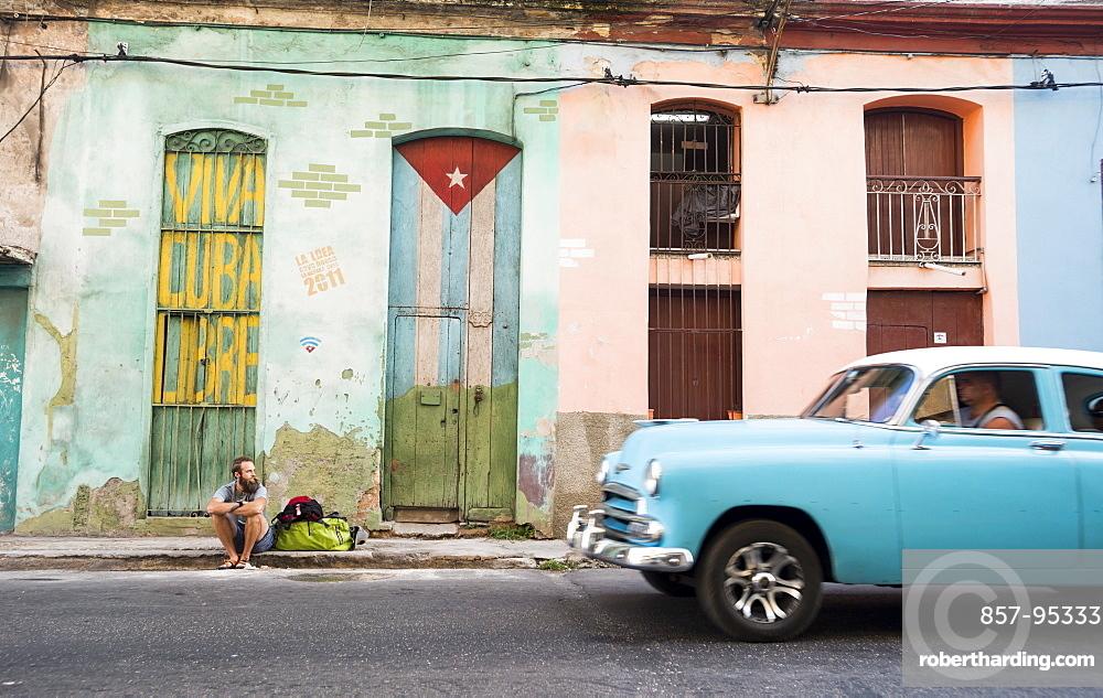 Side view of male tourist sitting on street of Havana, Cuba