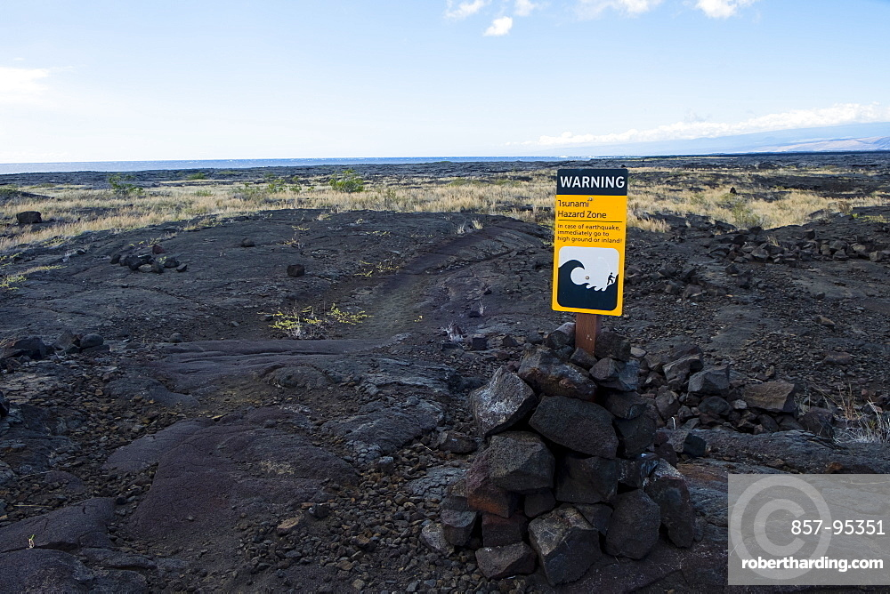 Tsunami Hazard Zone warning sign in bright yellow stands out from the landscape along the famed Puna Coast Trail to Halape Beach. The trail is 11.3 miles of rugged hiking for backpackers with no shade or water in the extreme terrain of Hawaii Volcanoes National Park, Hawaii, USA