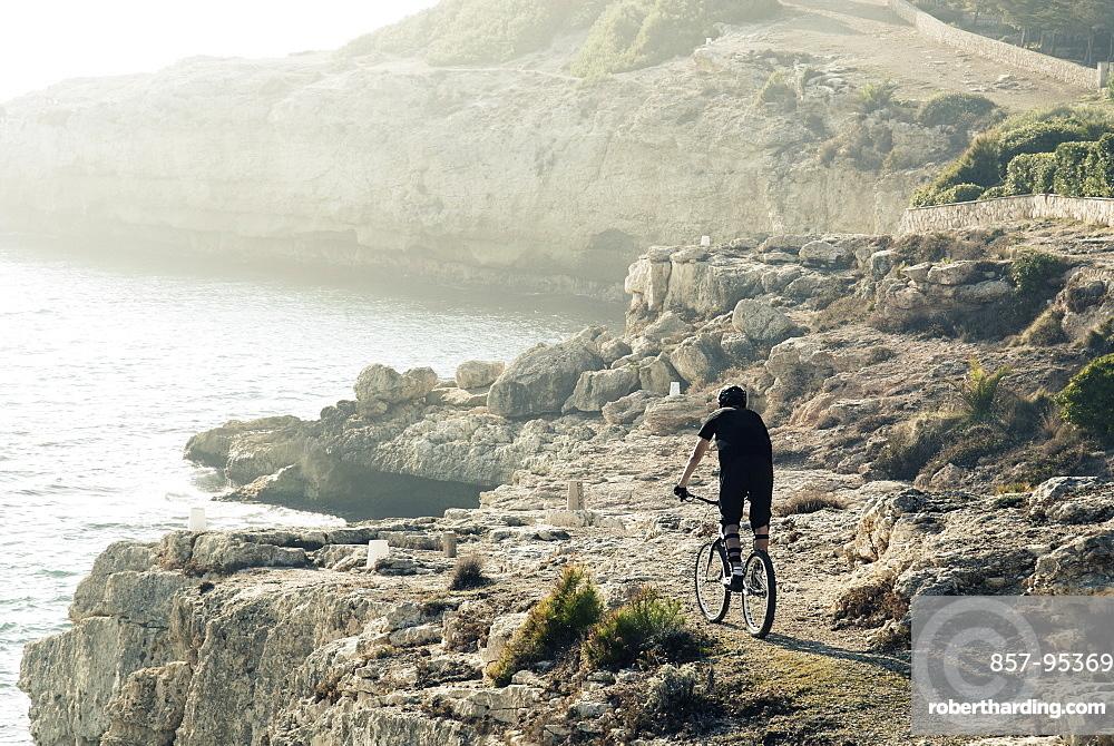 Rear view shot of adventurous mountain biker riding on coastal cliffs