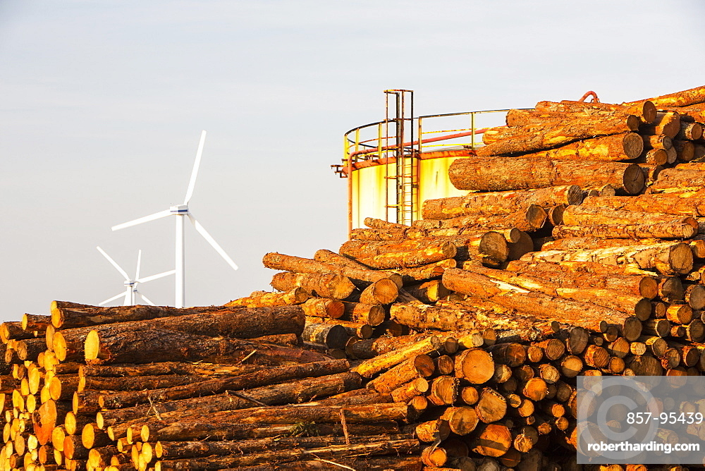 Logs bound for a biofuel power station in Workington next to oil tanks in Workington port, Cumbria, UK, with a wind farm in the background