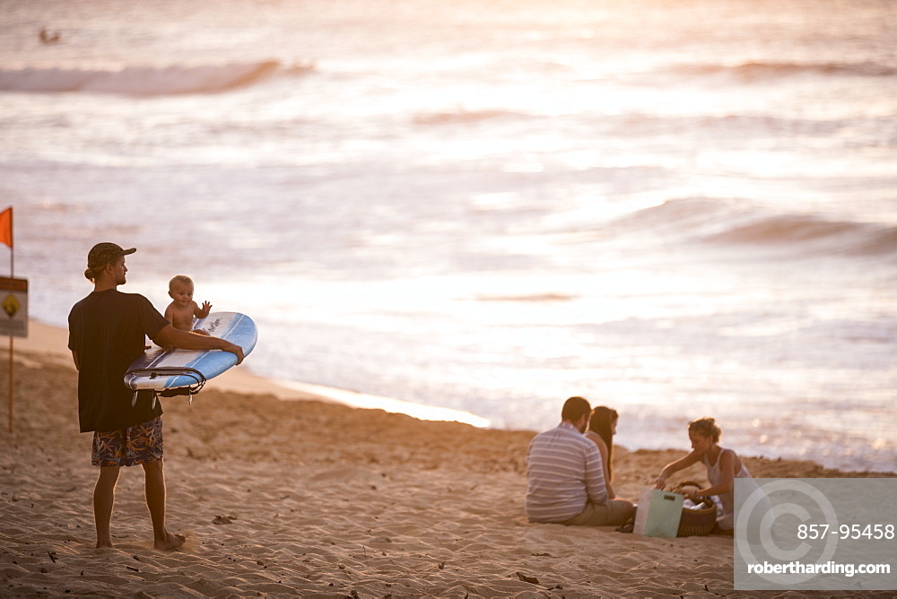 Surfer with baby on surfboard and other people on beach at sunset, Oahu, Hawaii Islands, USA