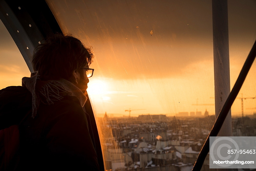 Man looking through window at sunset at view of Paris, France in Centre Georges Pompidou