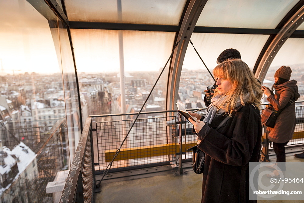 Tourists looking through window at view of Paris, France in Centre Georges Pompidou at sunset