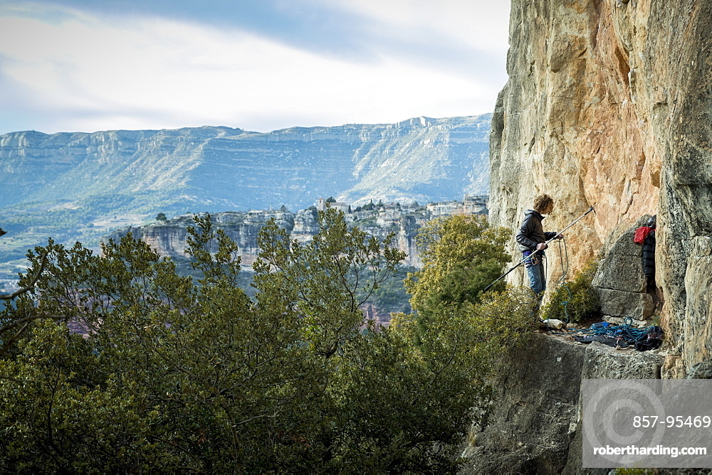 Distant view of single adventurous male rock climber preparing stick clip at cliff, Siurana, Catalonia, Spain