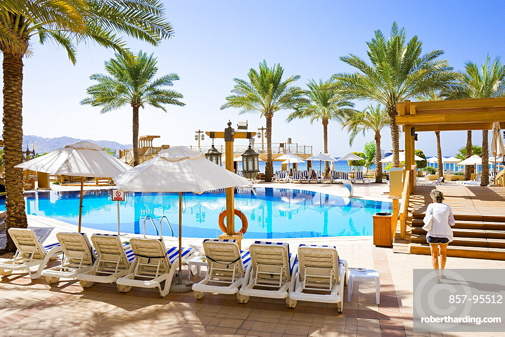 Woman walking by pool in tourist resort with palm trees, Aqaba, Jordan