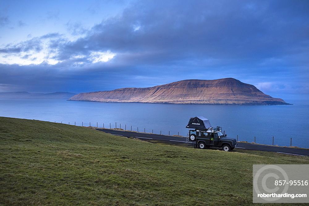 Side view of 4x4 car driving along coastline, Faroe Islands, Denmark