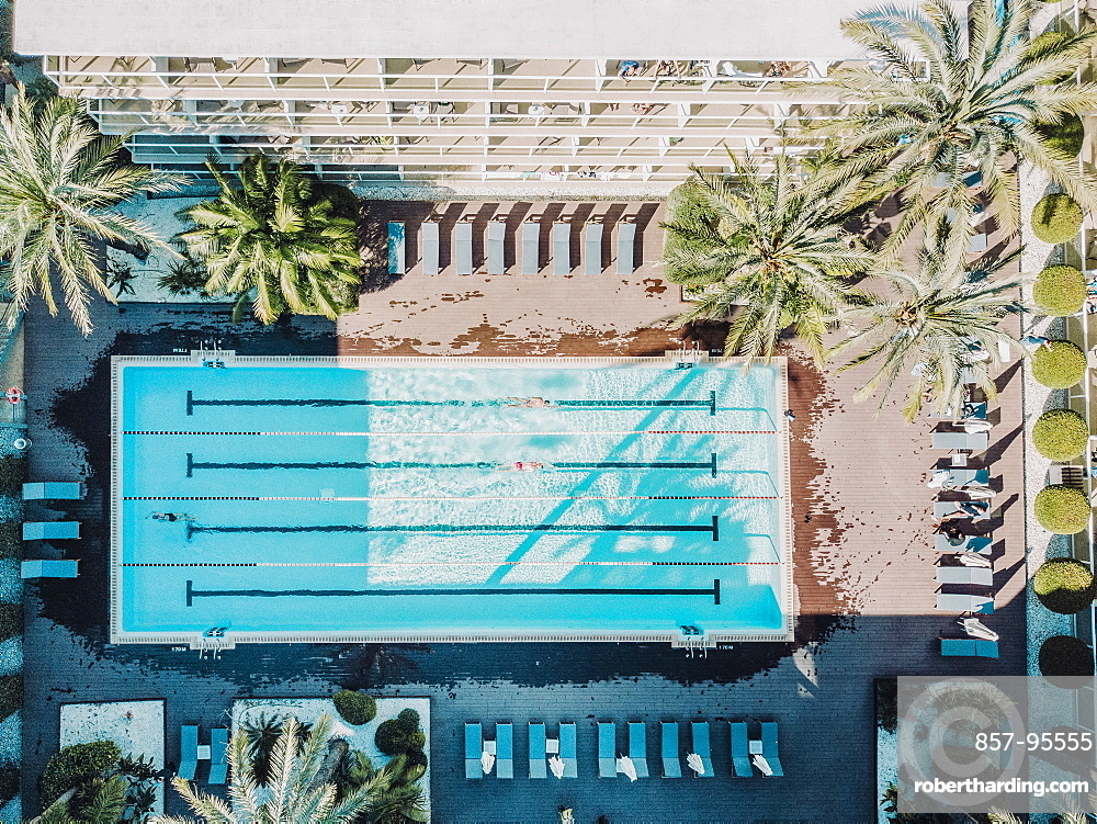 Aerial view of swimmers in hotel swimming pool at daytime, Mallorca, Balearic Islands, Spain