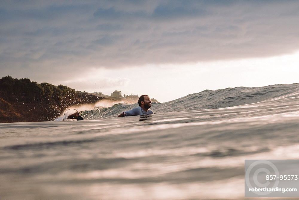 Professional surfer Jonathan Gonzalez paddling back to peak as sun sets, Tenerife, Canary Islands, Spain