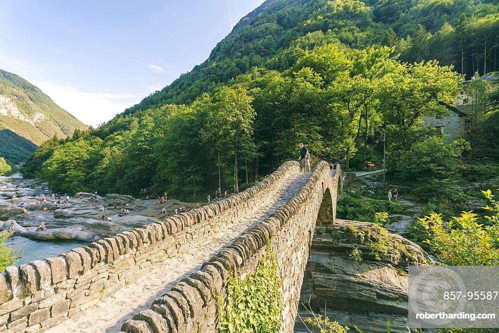 Mountainscape with stoned bridge across river in Alps in summer, Verzasca, Ticino, Switzerland
