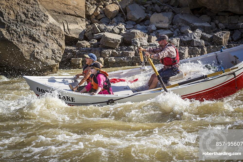 Man and two women sailing through rapids of Green River in Desolation Canyon, Utah, USA