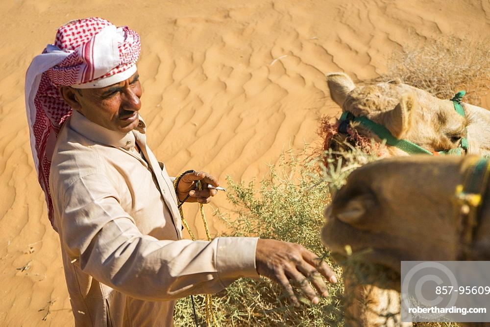 High angle view of man in Arabic clothing feeding camel in desert of Wadi Rum, Wadi Rum Village, Aqaba Governorate, Jordan