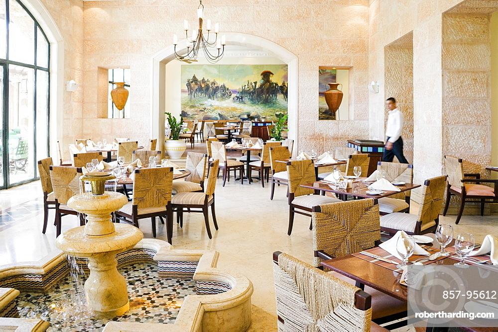 Waiter walking across luxurious Al Saraya Restaurant in Movenpick Dead Sea Spa and Resort, Madaba Governorate, Jordan