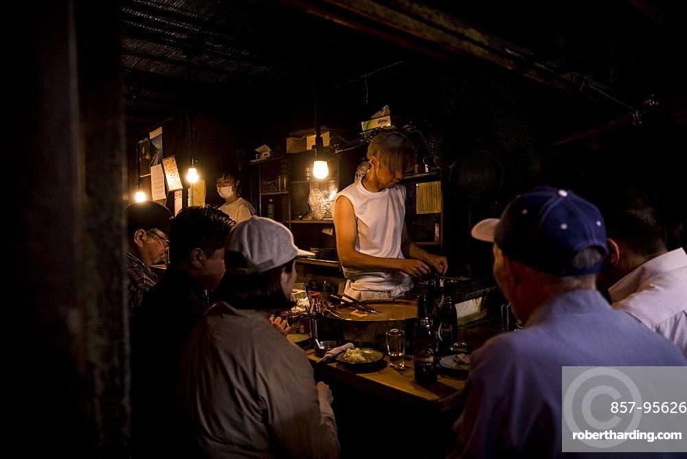 Customers sitting and waiting for food at small market, Tokyo, Tokyo, Japan