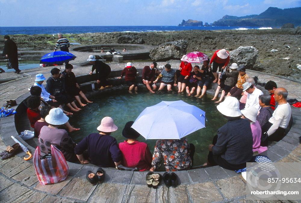 People enjoying saltwater hot springs on sunny day, Lu Tao, Lu Tao Island, Taiwan