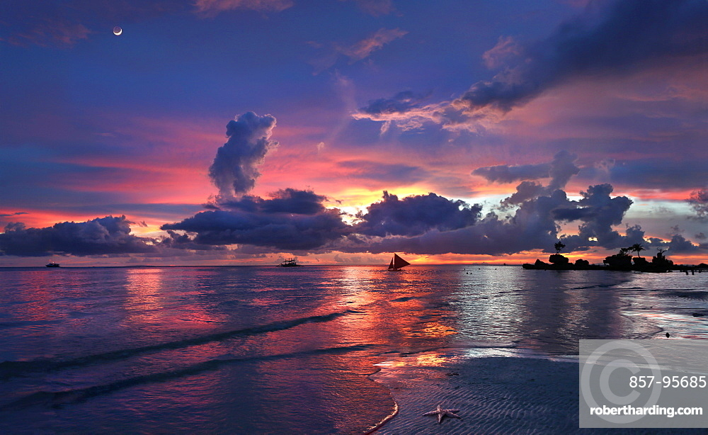 Tranquil scene with beach and sea at sunset with silhouettes of sailboats, Boracay, Aklan, Philippines