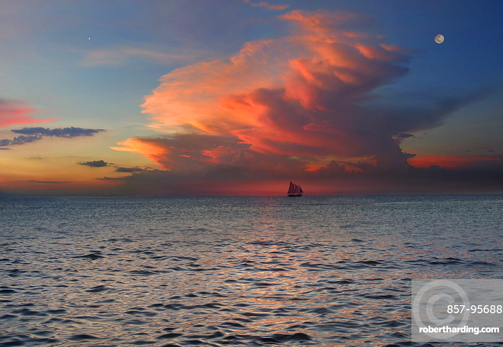 Distant view of sloop in sea under moody sky at sunset, Boracay, Aklan, Philippines