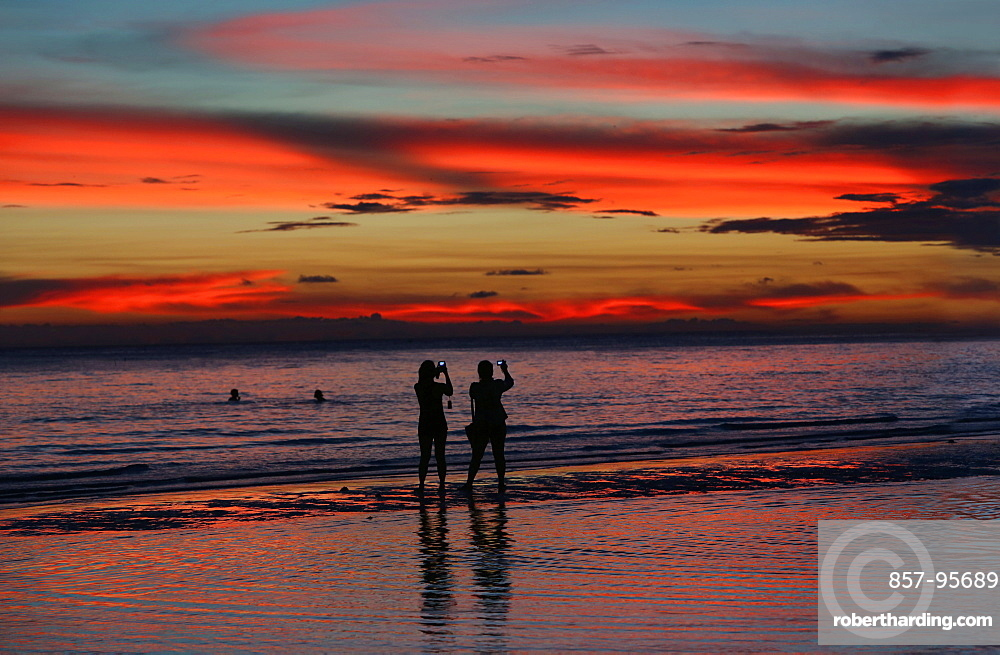 Silhouettes of two female tourists photographing sunset on beach, Boracay, Aklan, Philippines