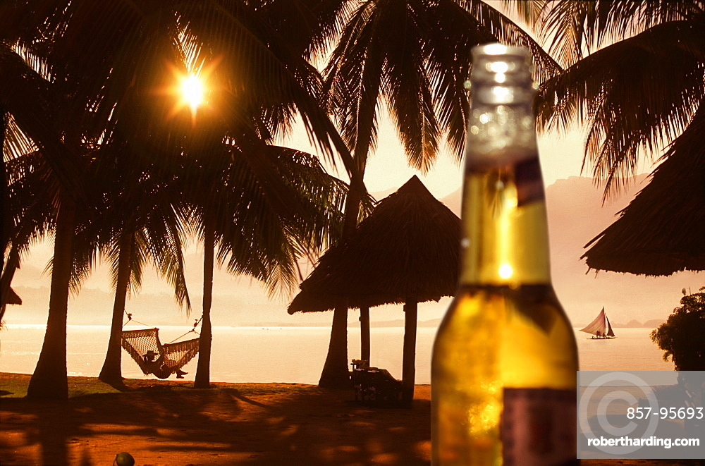Beer bottle against beach with palm trees and woman in hammock at sunset, Badian, Cebu, Philippines
