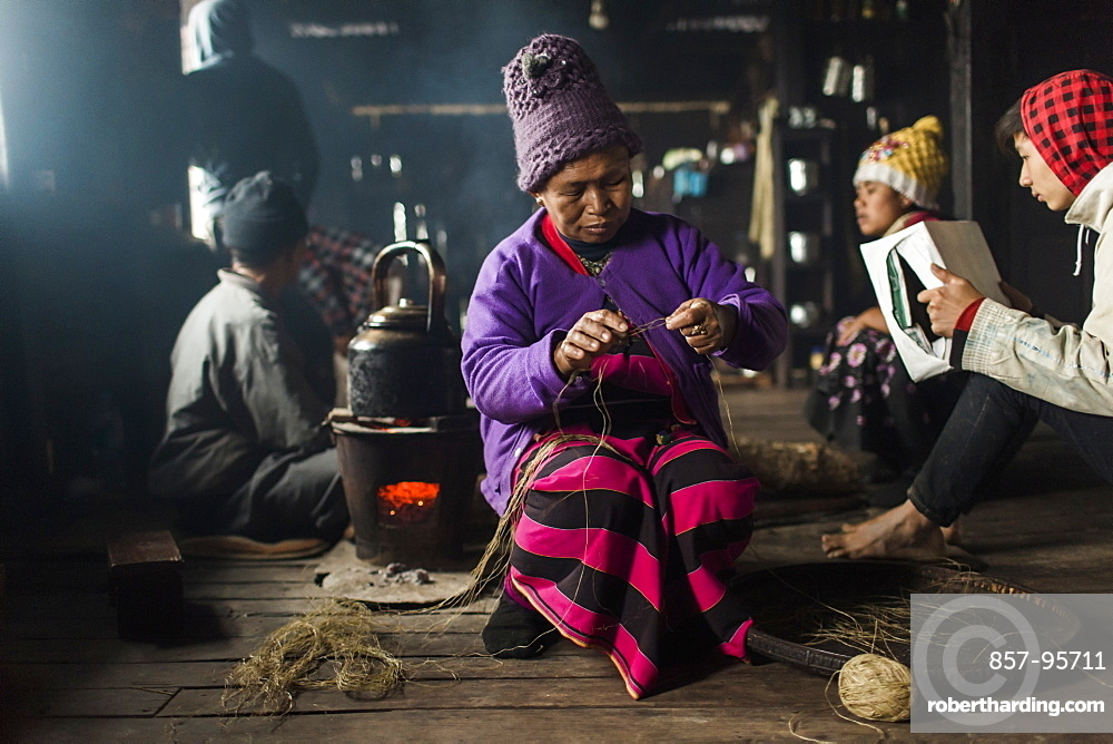 Elderly woman wearing knit hat knitting indoors in small rural house, Myanmar, Shan, Myanmar