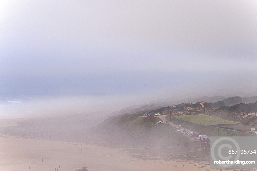 View of sandy beach and hill in fog at morning, Nazare, Leiria, Portugal