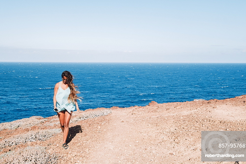 Woman walking on flat stretch of coast with ocean in background at daytime, Tenerife, Canary Islands, Spain